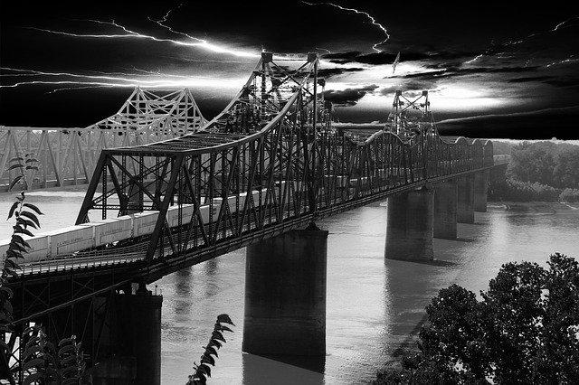 A black and white image of The Old Vicksburg one rail line and the new Vicksburg Bridge. A train passes along the near bridge.